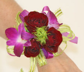 Red spray rose and fuchsia dendrobium orchid wrist corsage from The Posie Shoppe in Prineville, OR